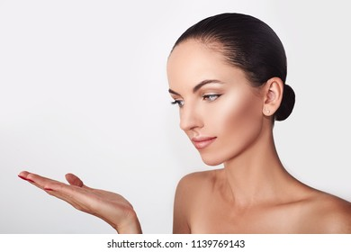 Beauty Spa Woman with perfect skin Portrait. Beautiful Brunette Spa Girl showing empty copy space on the open hand palm for text. Proposing a product. Gestures for advertisement.