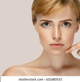 Beauty Spa Woman with perfect skin Portrait. Beautiful Blonde Red Hair Spa Girl Touching Face Hands Nails Manicure Proposing a product. Gestures for advertisement. Beige Pink background