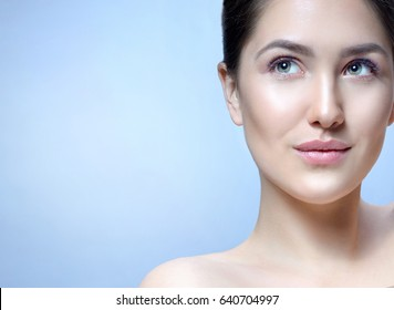 Beauty Spa Woman with Perfect skin Portrait. Young Caucasian with Fresh looking Skin Woman Face Closeup. Blue background. Looking up
