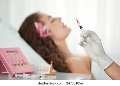 Beauty Spa: Young Beautiful Woman Having Cosmetic Injection of Botox . Selective Focus is on the Hand with Syringe