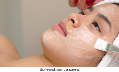 Beauty specialist uses brush to apply cosmetic mask on girl's face