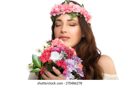 Beauty Spring Girl. Thoughtful Pretty Young Woman with Floral Ring on her Head Smelling a Bouquet of Fresh Spring Flowers with Eyes Closed. Isolated on White Background with Copy Space for Text