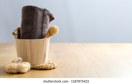 beauty still life concept with grey towel, face dry brush, loofah in wooden bucket for zero waste shower and indulging bath, copy space