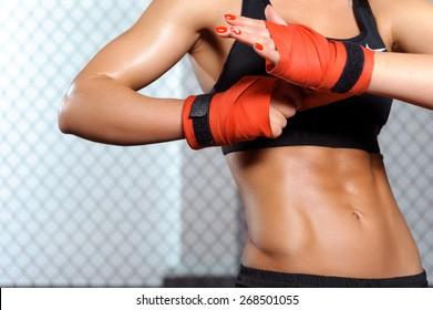 Beauty strikes. Close-up of a woman doing boxing bandages in a fighting cage