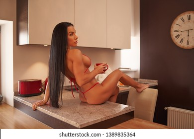 Beauty strong brunette fitness model in small bikini is drinking from a cup on a kitchen table