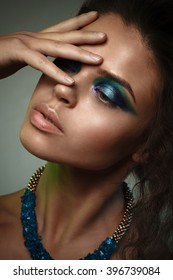 Beauty studio portrait of  sun-tanned woman with bright blue and green make-up.
