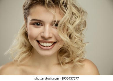 Beauty studio portrait of young happy optimistic cheery beautiful blonde  woman with perfect skin, make up and hairstyles, posing naked isolated over grey wall background.