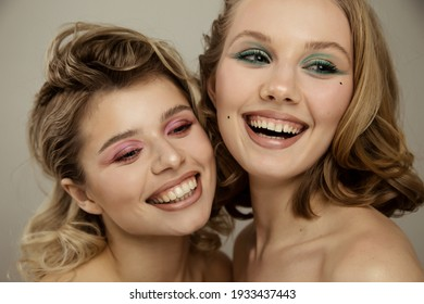 Beauty studio portrait of young happy optimistic cheery beautiful blonde  women with perfect skin, make up and hairstyles, posing naked isolated over grey wall background.