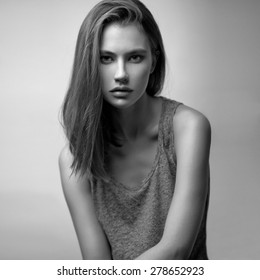 Beauty studio portrait of young stunning model in tank top with long straight hair. Black and white.