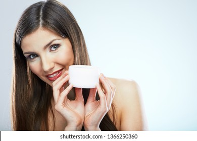 beauty style close up face portrait of young woman holding cosmetic cream in jar. isolated studio portrait.