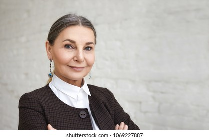 Beauty, style, fashion and age concept. Close up portrait of positive elegant 60 year old female with gray hair and wrinkled face posing against white brick wall background and smiling at camera