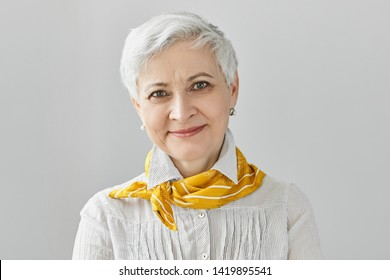 Beauty, style, fashion and aging concept. Charming elegant gray haired retired woman wearing stylish yellow silk scarf smiling happily, enjoying her mature age, not being afraid of getting old