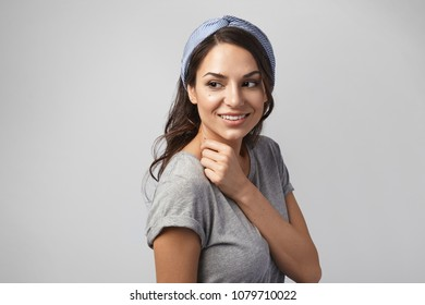 Beauty, style and fashion concept. Horizontal shot of beautiful stunning young woman model with tanned skin and long dark hair posing isolated in studio, smiling joyfully and looking sideways