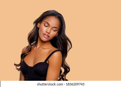 Beauty styled portrait of a young African - American woman. Fashion African - American girl with curly hair posing in the studio on a beige background. isolated. Studio shot.
