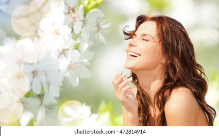 beauty, summer, emotion, expression and people concept - happy beautiful woman over natural spring cherry blossom background