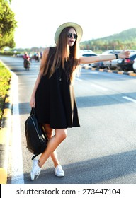 Beauty Sunshine Girl Portrait in little black dress,fashion look . Pretty happy woman enjoying summer outdoors. Sunny Summer Day under the Hot Sun on the road.young stylish traveler in casual clothes