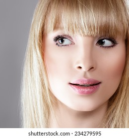 Beauty surprised blonde woman against gray background