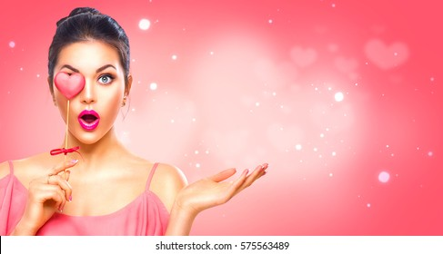 Beauty surprised Young fashion model Girl with Valentine Heart shaped cookie in hand. Love. Beautiful young woman pointing hand, advertising gesture. Valentines Day gift. Pink polka dots background