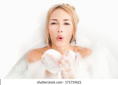 Beauty taking bath. Playful young woman lying in bathtub full of soapy lather and blowing an air kiss