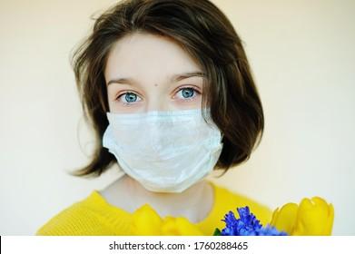 Belle adolescente avec de grands yeux bleus sur le visage masqué de fleurs pendant la pandémie à l'extérieur