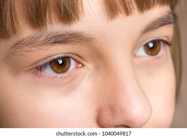 Beauty teen girl face close up portrait. Young cute child with brown eyes, looking away.
