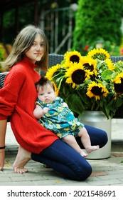 Belle adolescente avec sa petite soeur sur l'arrière-cour avec un grand bouquet de tournesols