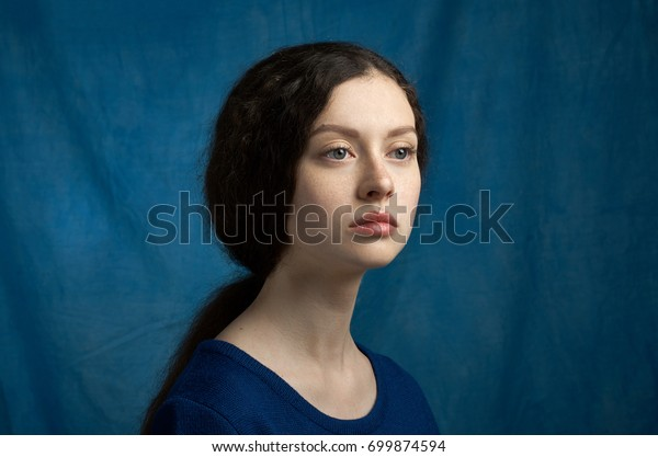 Beauty theme: portrait of a beautiful young girl with freckles on her face and wearing a blue dress on a blue background in studio
