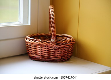 The beauty of  this still life is its simplicity. A plain wicker basket placed on a  window seat in in the corner against  a mustard colored wall  and the window. This clearly says country.