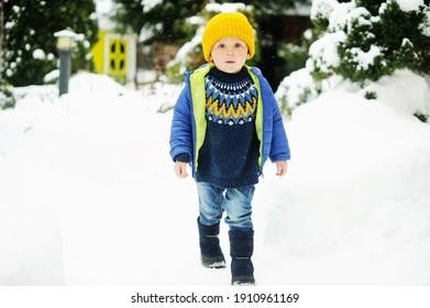 Belle petite fille en vêtements d'hiver colorés en chapeau jaune et veste bleue jouant dehors dans la neige le jour d'hiver