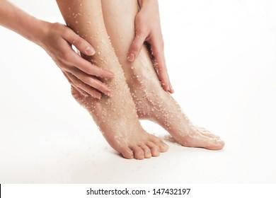 Soins de beauté pour les jambes. Mains massantes pieds avec sel de mer. Tournage en studio.