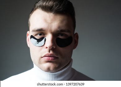 Beauty treatment. Skin care. Metrosexual concept. Focused treatments for under eye area. Minimizes puffiness and reduce dark circles. Eye patches for men. Man with black eye patches close up face.