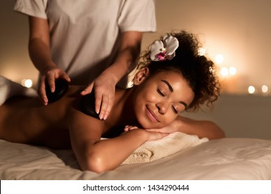 Beauty Treatment Therapy. Woman Getting Hot Stones Arm Massage In Spa Salon