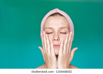 Beauty Treatments. A young woman is applying a mask, a cream on her face with her hands close up, washing herself with water with her hands closed. Facial skin care portrait of a beautiful girl with a