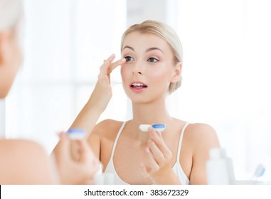 beauty, vision, eyesight, ophthalmology and people concept - young woman putting on contact lenses at mirror in home bathroom