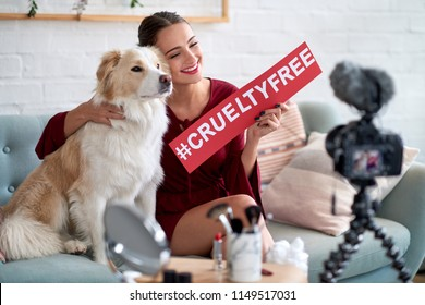 Beauty vlogger influencer hugging dog promoting cruelty-free cosmetics, against animal testing social issue