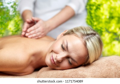 beauty, wellness and relaxation concept - beautiful young woman lying having back massage in spa over green natural background
