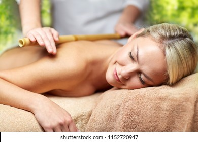 beauty, wellness and relaxation concept - close up of beautiful young woman lying with closed eyes and having bamboo massage in spa over green natural background