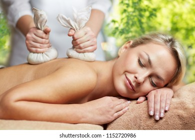 beauty, wellness and relaxation concept - close up of beautiful young woman lying and having herbal bag massage in spa over green natural background