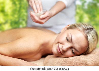 beauty, wellness and relaxation concept - close up of beautiful young woman lying with closed eyes and therapist holding salt bowl in spa over green natural background