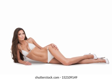Beauty in white bikini. Beautiful young woman in white bikini lying on side and looking at camera while isolated on white