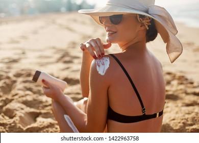 Beauty Woman applying sunscreen creme on tanned shoulder. Skincare. Body Sun protection suncream. Bikini hat woman applying moisturizing sunscreen lotion on back.