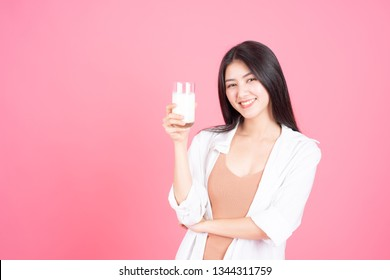 beauty woman Asian cute girl feel happy drinking milk for good health in the morning on pink background - lifestyle beauty woman c