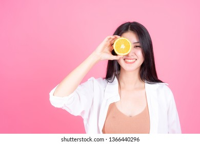 beauty woman Asian cute girl feel happy holdind orange fruit for good health  on pink background - lifestyle beauty woman