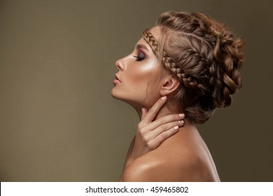 Beauty woman with beautiful make-up color . Brown hair , braids of hair, clean shiny skin , beauty face . Portrait shot in studio on a green background .