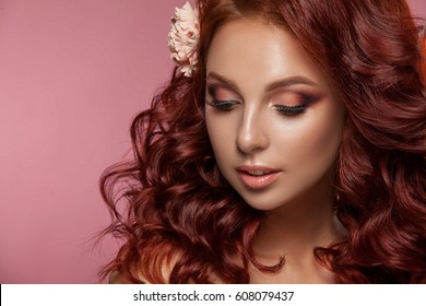 Beauty woman with beautiful make-up color . Red hair , raised hair , jewelry on his neck , clean skin , beautiful face . Portrait shot in studio on a red background .