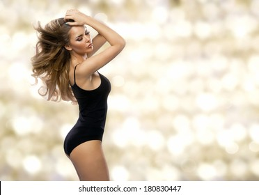 Beauty woman in black lingerie on gold background
