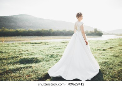 Beauty woman, bride with perfect white dress posing on the rock background mountains