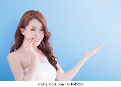 Beauty woman with charming smile and show something to you with health skin and hair isolated on blue background, asian beauty