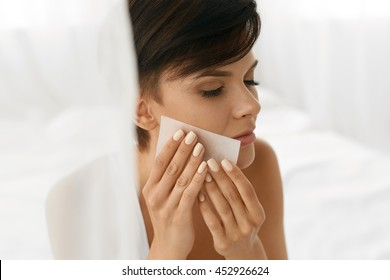 Beauty. Woman Cleaning Perfect Fresh Skin With Oil Absorbing Tissue, Sheets. Closeup Portrait Of Beautiful Healthy Girl With Nude Makeup Removing Oil From Face Using Blotting Papers. Skin Care Concept