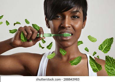 beauty woman cleaning teeth surrounded leavs of mint